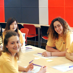 Three female ALSS student ambassadors sitting around a table
