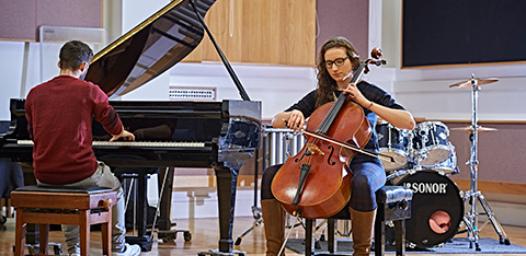 Male student playing the piano and female student playing the double bass