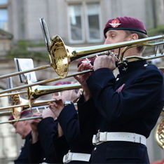 A member of the Band of the Parachute Regiment standing playing the trumpet