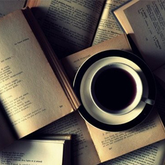 A cup of coffee resting on open books