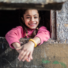 a portrait of a young girl, looking at the camera and smiling. photo by Anna Kressler