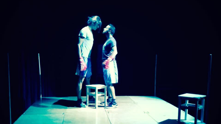 Two male actors on-stage playing boxers facing each other down