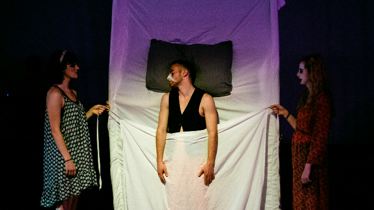 A male actor on-stage in a vertical bed, a sheet held in front of him by two female actors
