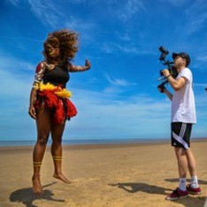 An African tribeswoman dances in front of a cameraman