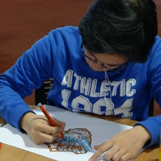 A young artist drawing a football team badge design