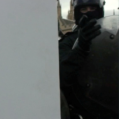 A riot police officer next to a blank, grey space.