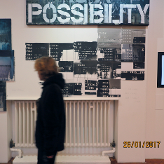 A gallery visitor looking at paintings in a gallery beneath a sign that reads 'Possibility'