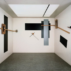 A white exhibition space with various pieces of wood, metal and black and grey rectangles on the walls