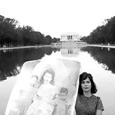 A woman holding a family portrait in front of the Lincoln Memorial
