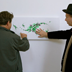 Two men touching a green painting on a wall.