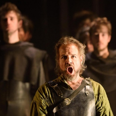 A male opera singer in a metal breastplate performs Guilio Cesare with a choir behind him
