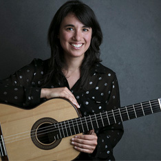 a portrait of a woman, smiling and holding a guitar
