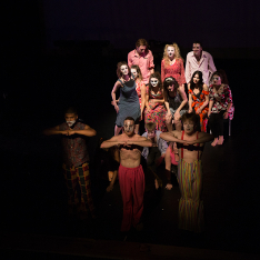 Performing Arts students spotlit on stage in costume