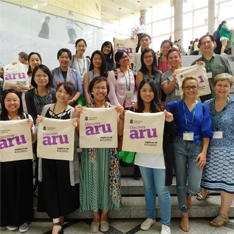 International graduates from Anglia Ruskin's MA Music Therapy standing for a group photo, holding up ARU canvas bags, at a conference in Japan