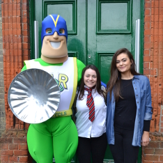 A costumed superhero holding a bin lid as a shield with two female drama students outside the Covent Garden Drama studio in Cambridge