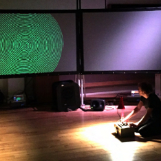 Fredrik Olofsson projecting a green spiral onto a screen during a concert