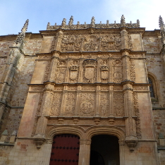 Front of the University of Salamanca, an ornate building with shields and carvings