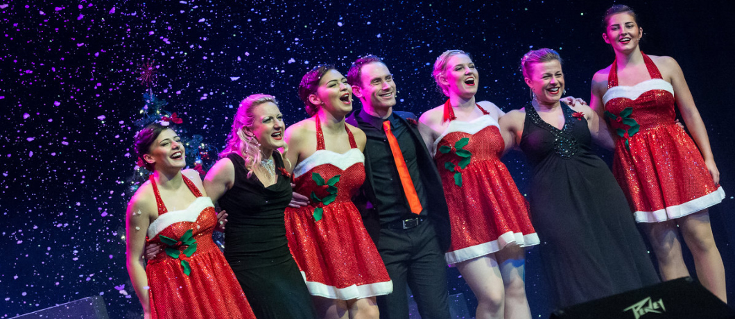 A group of men and women in festive dress, stood on stage in a line, taking a bow