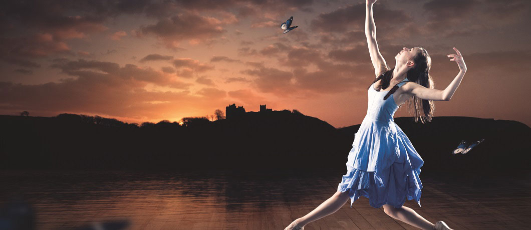 A ballerina, held in a pose, set against a sunset with a castle in the background. Butterflies are flying around her.