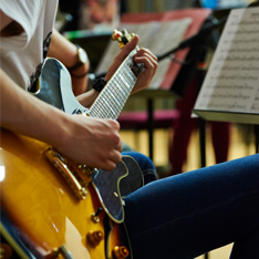 A closeup of a student sitting down playing the guitar