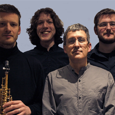 Four men stood looking at the camera, one holding a clarinet