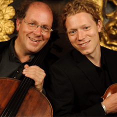 Two men smiling at camera while holding musical instruments