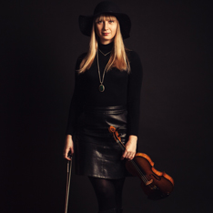 a photo portrait of a woman dressed in black, wearing a hat and holding a violin