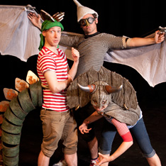 three actors, dressed as dinosaurs, strike a pose for the camera