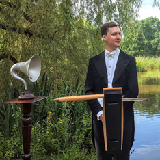 a man stood posed with a theremin, outside in front of a lake