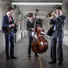 Three smartly dressed musicians, playing whilst standing in a walkway