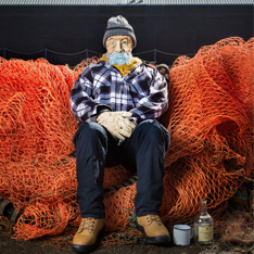 a large man-sized puppet dressed as a fisherman sat on a bundle of nets