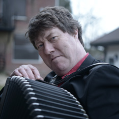 A close-up portrait photo of Jon Banks, holding an accordian