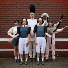 a group of performers stood against a red brick wall, posing, wearing silly hats and wigs
