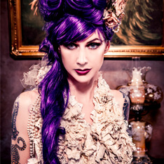 a portrait of a tattooed woman with striking purple hair