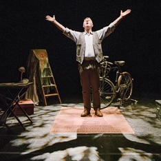 an actor on stage, arms outstretched, stood amongst props including a bike, stepladder and desk