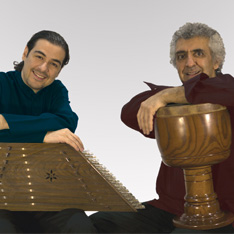 Two men with musica instruments, smiling at the camera