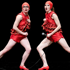 two women in matching red costumes and swim caps, striking a pose