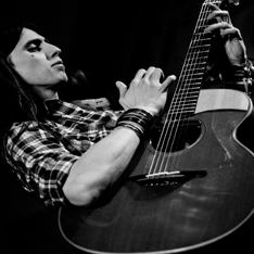 a black and white image of a man, playing the guitar