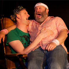 a large bearded man is sat in the lap of another man wearing a crown - they are both laughing and joking