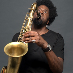 Soweto Kinch, holding and playing a saxophone