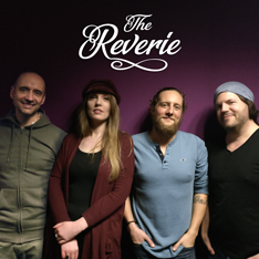 Four people, three men and one woman, stood in a row looking at the camera and smiling. The logo for The Reverie is set above them.