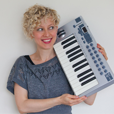 a woman stood posing and smiling, holding an electric keyboard