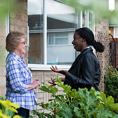 A nurse and a patient discussing on doorstep