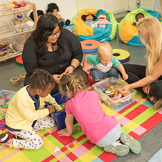 two nursery workers with young children in a play room