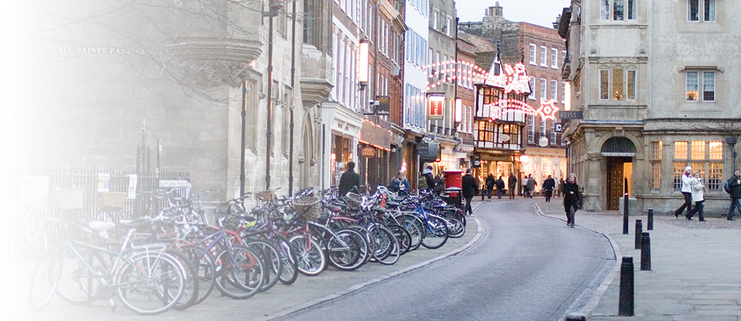 Street in Cambridge showing parked bikes and buildings with fairy lights hanging outside.