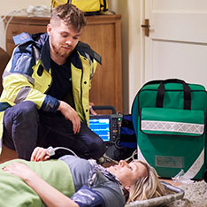 paramedic student examining lady laying on floor