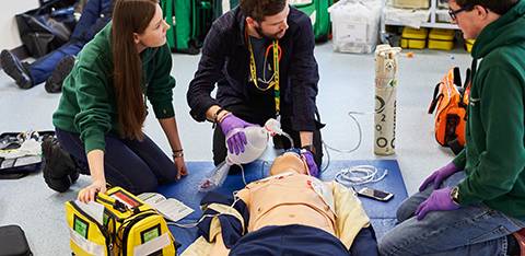 Paramedic students practicing on medical mannequin