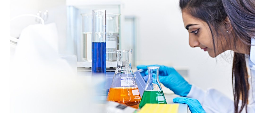 Woman looking at liquids in a lab