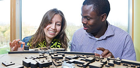 Two students discussing an architecture model