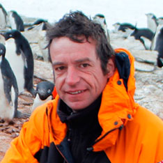 Head shot of Anglia Ruskin lecturer, Fabrizio Manco, crounching in the South Orkney Islands in front on chinstrap penguin colony.